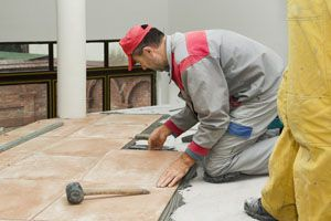 Interior rehabilitation when construction worker is installing ceramic tiles in Lemont