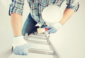 Interior renovation when worker is painting a white wall with paintbrush and pot on ladder in Naperville